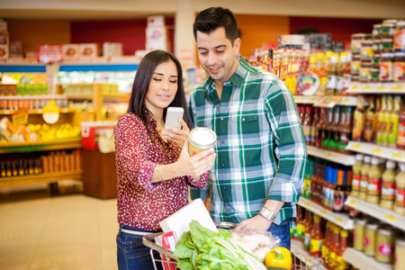 mobile app: Pretty young brunette and her partner taking a picture of a product with her cell phone at a grocery store Stock Photo