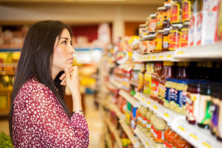 thinking woman: Beautiful brunette looking at some shelves in a supermarket trying to decide what to buy Stock Photo