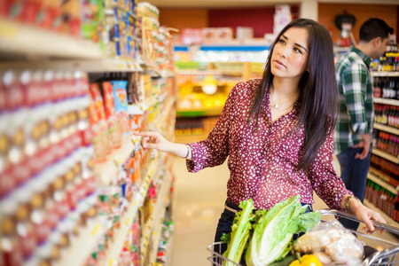 woman shopping cart: Pretty young Latin brunette picking up some food at the grocery store