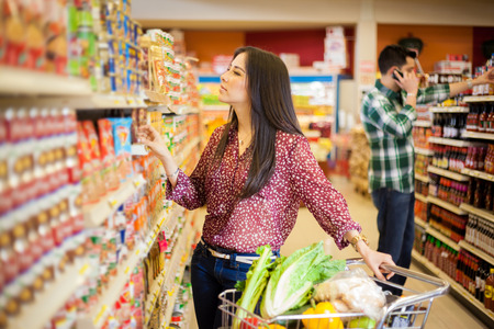 スーパー マーケットの通路上のいくつかの製品を見て、ショッピング カートの豪華な若い女性 写真素材
