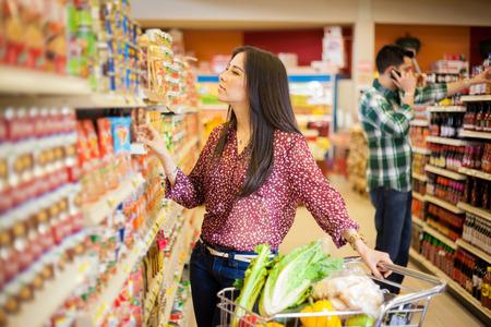 Gorgeous giovane donna con un carrello della spesa, cercando in alcuni prodotti su un corridoio supermercato Archivio Fotografico - 26683579