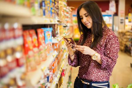 persona leyendo: Linda joven examinar una etiqueta del producto mientras que las compras en la tienda Foto de archivo