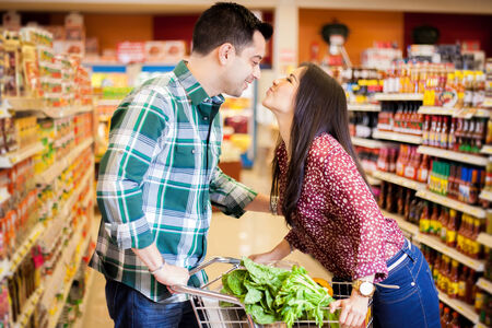 Cute young couple kissing each other across a shopping cart at the supermarket