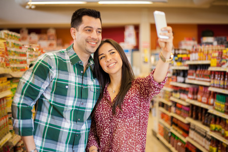 tiendas de comida: Feliz pareja de j�venes tomando un selfie con un tel�fono inteligente mientras que las compras en el supermercado