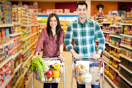 Young newlyweds buying some groceries together and smiling photo