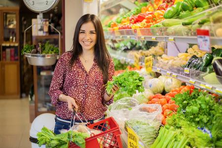 식료품 가게에서 몇 가지 야채를 쇼핑 바구니를 들고 따기 행복 젊은 갈색 머리