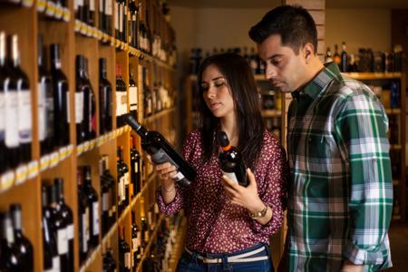 tiendas de comida: Hermosa pareja hispana de elegir una botella de vino en una bodega