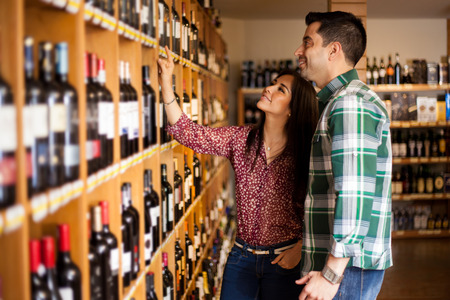 Young Latin couple deciding which wine to buy at the supermarket photo
