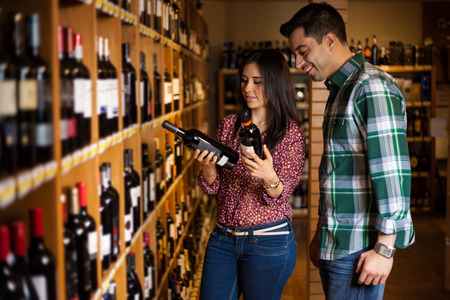 woman shopping cart: Cute young Hispanic couple trying to decide which bottle of wine to buy among so many options
