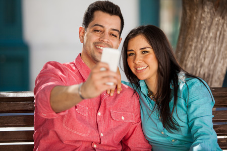 Pretty young couple taking a selfie with their smart phone while sitting on a park bench photo