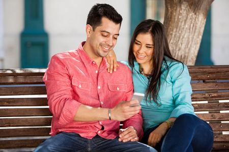 Happy young couple sitting in a park bench and using a smart phone photo
