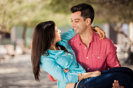 carrying: Handsome young Hispanic man carrying her girlfriend and smiling outdoors Stock Photo