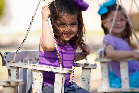 Cute little friends having fun on a swing at a park and smiling photo