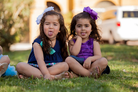 pull out: Cute little friends having fun together and pulling out their tongues