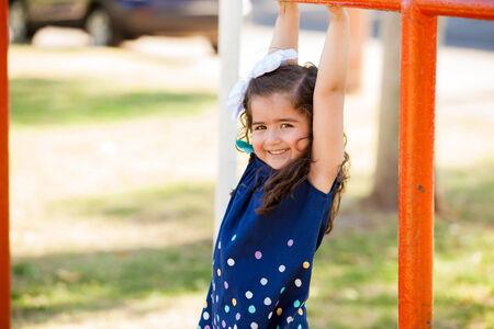 niños jugando en el parque: Feliz niña hispana colgando de algunos manillares en un parque Foto de archivo