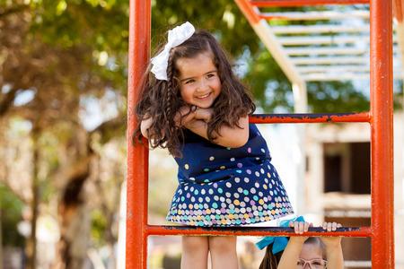 niños jugando en el parque: Niña dulce que se divierte en un parque en algunos manillares Foto de archivo