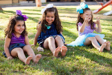 human toe: Barefoot little sisters wiggling their toes and having fun at a park Stock Photo