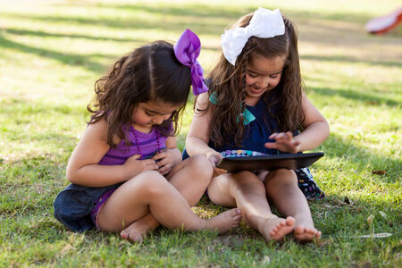 latin child: Cute little sisters using a tablet computer at a park on a sunny day Stock Photo