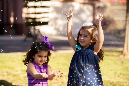 latin child: Little sisters having fun with some foam that looks like snow at a park