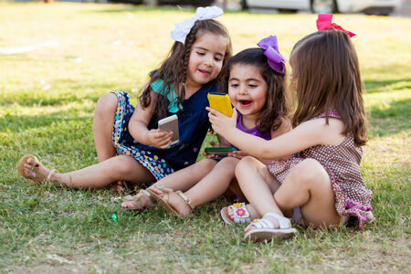 Funny little girls sharing some stuff from their smart phones and having fun photo