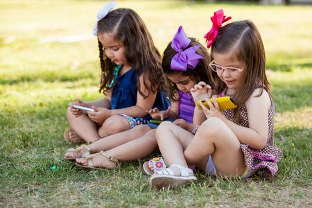 Schattige kleine zusjes spelen met hun eigen telefoon en het negeren van elkaar in een park