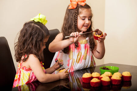 decorating: Cute brunette and her sister decorating some cupcakes with chocolate at home