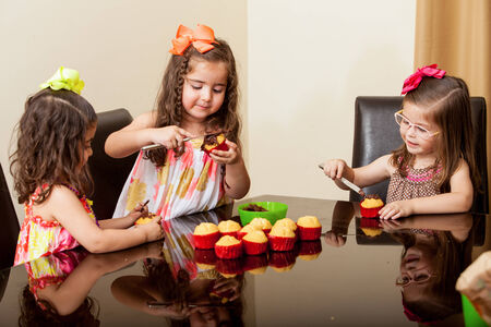 decorating: Pretty little girls baking and decorating cupcakes together at home
