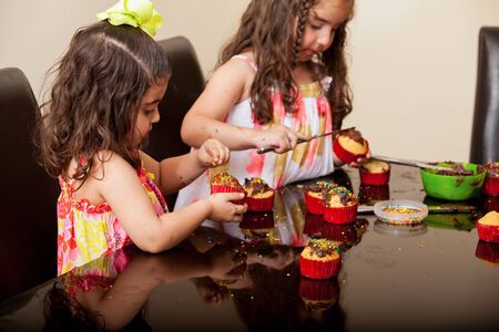 decorating: Little Hispanic girl and a friend decorating cupcakes with sprinkles