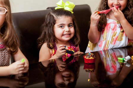 three wishes: Gorgeous little girl celebrating her birthday with her friends and a cupcake