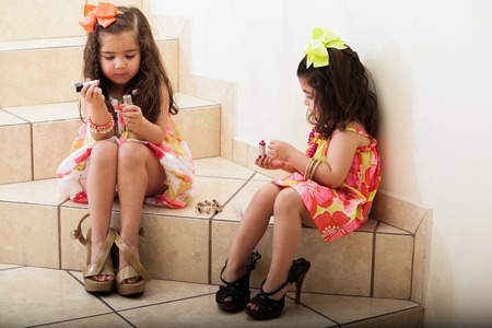 Cute naughty little sisters stealing some makeup from their mom and putting it on photo