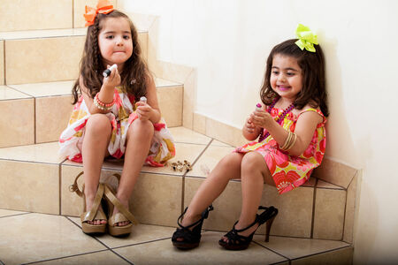 Happy little friends having fun trying on some lipstick and their moms photo