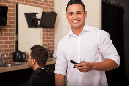barber scissors: Handsome young Latin barber loving his job and smiling