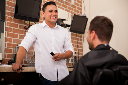 Happy barber talking with a customer and having a good time at work photo