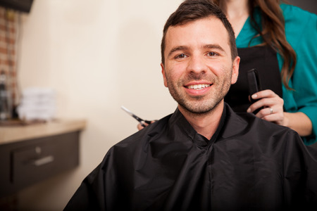 Young Hispanic man getting a haircut at a hair salon and smiling photo
