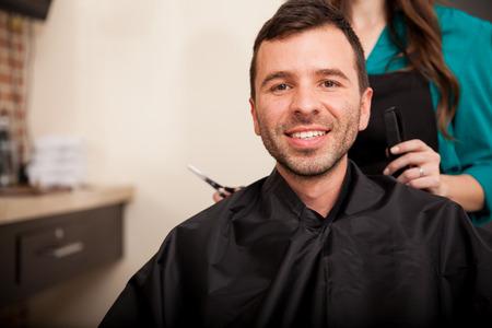 haircut: Young Hispanic man getting a haircut at a hair salon and smiling