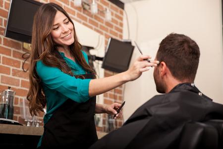 Pretty female barber cutting a man photo