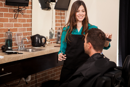 barber: Cute brunette giving a haircut to a client in a barber shop