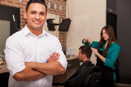 ハンサムな若い理髪店のオーナーは微笑し、彼のビジネスを管理します。