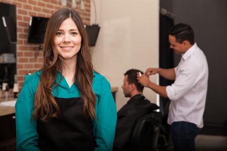 barber shop: Leuke jonge vrouw die het beheer van haar kapperszaak en glimlachen Stockfoto