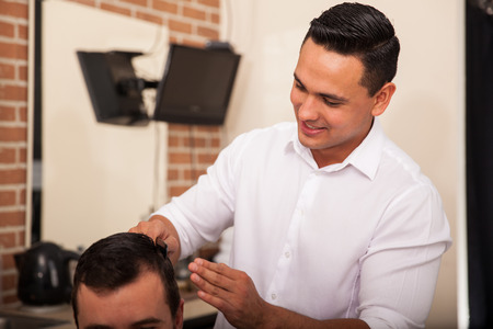 haircut: Young Latin barber giving a haircut to a client