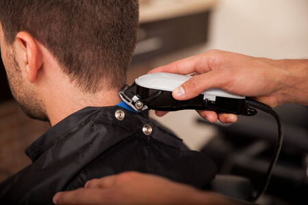 Closeup of a barber using hair clippers on a customer photo