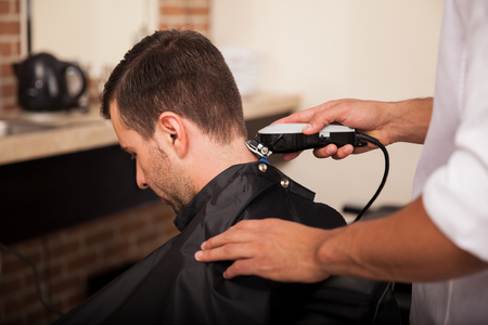 Male hairstylist using hair clippers on a customer at a hair salon photo