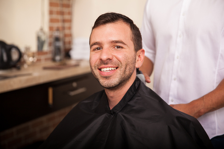haircut: Handsome young man getting a haircut at a barber shop and smiling Stock Photo