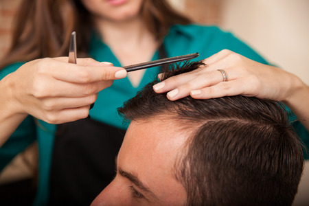 haircut: Closeup of a young hairstylist giving a haircut to a customer in a hair salon Stock Photo