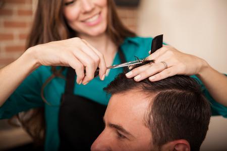 haircut: Cute hairstylist giving a haircut and enjoying her work at a hair salon