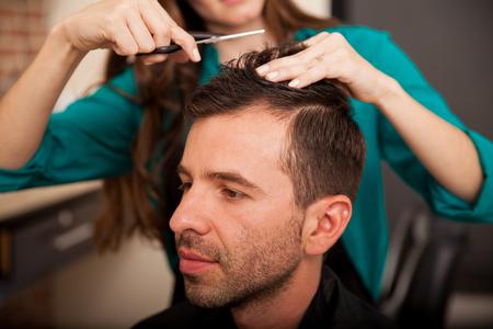 haircut: Portrait of a young Hispanic man getting a haircut at a barber shop
