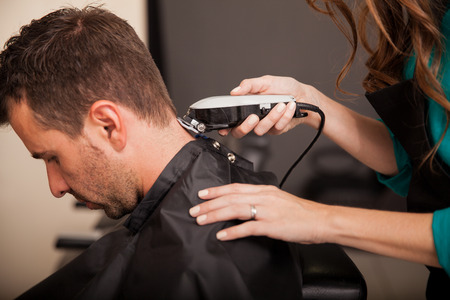 cutting hair: Young man getting a haircut at a hair salon