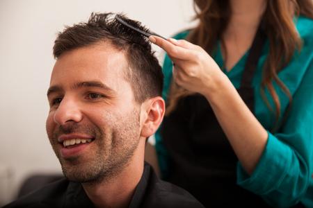 haircut: Young Latin man loving his new haircut in a hair salon Stock Photo