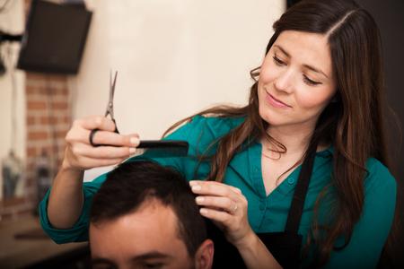 haircut: Beautiful young woman giving a haircut to a customer in a hair salon