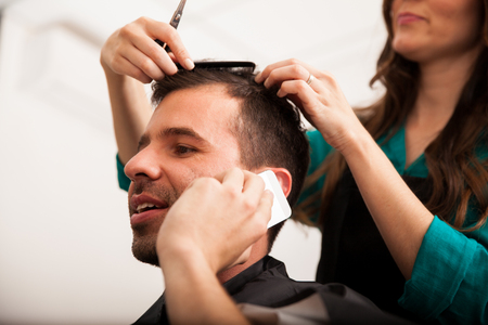 haircut: Young handsome man talking over the phone while getting a haircut in a barber shop Stock Photo